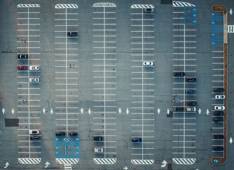 An aerial view of parking lot with cars and road marks