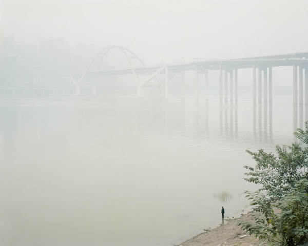 Fisherman in the mist at Cayiuanba Changjiang Bridge. Yuzhong District. Chongqing. China. December 2017  Chongqing is almost permanently covered in a thick mist, a mix of damp and pollution, which makes it one of the least sunny cities in the country. Along the banks of the Yangtze, which are still wild in many places, fishermen go about their business despite highly polluted water.